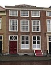 foto van Huis onder schilddak en met gepleisterde lijstgevel, waarin korte zolderverdieping