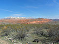 A photo of the Red Cliffs with snow-capped Pine Valley Mountains in the background