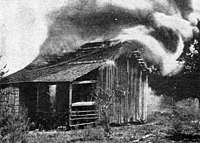 A black and white photograph of a crude wooden structure that could be a small shed, animal house, or hunting cabin with smoke pouring from it and flames visible in the door