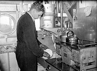 Short Sunderland - A crew member of a Short Sunderland Mark I of No. 10 Squadron RAAF, washing up in the galley during a flight.
