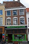 foto van Winkel met bovenwoning met lijstgevel en jongere winkelpui in de stijl van de Amsterdamse School
