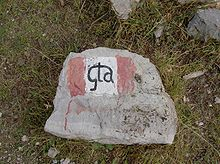 "Rock with painted red-and-white flag and ""GTA"" in center"