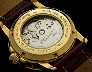 Automatic watch - Backside view of an automatic watch with a transparent case back, showing its movement. The semicircular rotor which winds the mainspring is plainly visible.