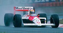 Un'auto F1 arancione e bianca guidata da Ayrton Senna