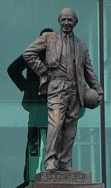 Une statue en bronze d'un homme chauve vêtu d'un costume.  Sa main droite est sur sa hanche droite et il tient un ballon de football sur sa hanche gauche.