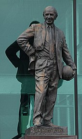 "A bronze statue of a smiling bald man holding a football at his left hip and with his right hand on his waist. The plinth reads ""Sir Matt Busby""."