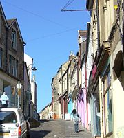 Street scene showing narrow cobbled road past coloured shop fronts