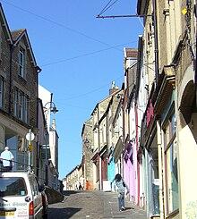 Stratsceno montranta mallarĝa flikis vojon pasintajn kolorajn butikfrontojn