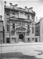 Old photo of the front of the former Hall showing its complex details. It was built of brick with a rusticated basement, balconies with curved wrought iron balustrades, a large entrance stairway under a prominent pediment and Art Nouveau panels.