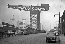 A black and white picture of a large crane reaching over a cargo ship.