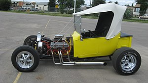 T-bucket - Convertible T-bucket in a hybrid style: traditional sidepipes and dropped tube axle, transverse front leaf spring, and non-traditional front disc brakes and five-spokes.