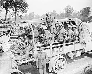 "16th (Irish) Division - Men of the 16th (Irish) Division (possibly of the 47th Brigade) in a lorry going back for a rest after taking Guillemont, 3 September 1916. They are passing by the ""Minden Post"" on the Fricourt-Maricourt road, west-south-west of Carnoy. Note some soldiers wearing captured German pickelhaubes and feldmutzes. Two soldiers clearly display cap badges of the Royal Irish Regiment."