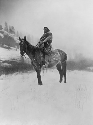 Crow scout on horseback