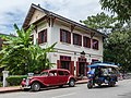 Three quarter view of Hotel 3 Nagas with a tuk-tuk and an old red Citroen in Luang Prabang Laos.jpg