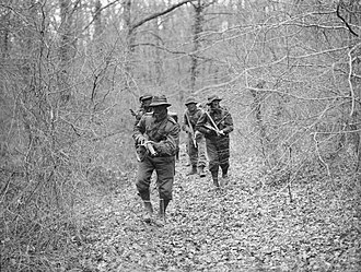 Brockenhurst - 2 February 1945. Royal Marine/Royal Navy trainees, their faces covered with camouflage paint and wearing US-style fatigue caps and gaiters, during training at the Eastern Warfare School, learning jungle tactics, before deployment to the Pacific War.