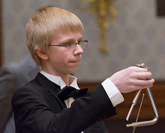 Triangle (musical instrument) - A young orchestral musician plays the triangle.