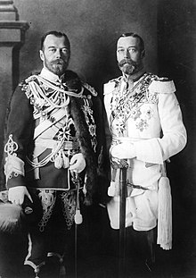 Two look-alike men. Both wear beards and are in full military regalia festooned with medals—one uniform dark, the other white.