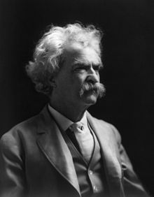 Photograph of man with a shock of white hair and a white mustache, wearing a three-piece suit. He is looking off to the right.