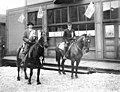 Two men on horseback with sashes and ribbons in front of building flying American flags, Nome, circa 1920 (AL+CA 6492).jpg