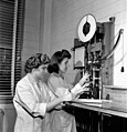 Two workers from Hamilton, Ontario, testing the tensile strength of a piece of synthetic rubber (33999400280).jpg