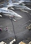 U.S. Sailors and Marines fuel an F-A-18C Hornet aircraft, left, assigned to Strike Fighter Squadron (VFA) 146 and an F-A-18C Hornet assigned to Marine Fighter Attack Squadron (VMFA) 323 on the flight deck of 130615-N-KE148-118.jpg