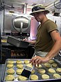 US Navy 030418-N-0728B-002 Mess Specialist 2nd Class Charles Mansfield assigned to Naval Hospital Pensacola on detachment to Fleet Hospital Three (FH-3), puts the finishing touch on a batch of biscuits before placing them in th.jpg
