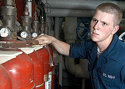A sailor in coveralls wipes down red gas bottles