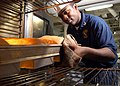 US Navy 040701-N-7748K-016 Culinary Specialist 3rd Class Jermaine Thompson, of Fayetteville, N.C., removes bread from an oven.jpg