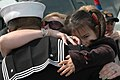 US Navy 060309-N-9562H-043 Seaman Paul Martinez hugs his wife and daughter after returning from a six-month deployment aboard the guided missile destroyer USS Donald Cook's (DDG 75).jpg