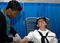 US Navy 060526-N-7292N-005 In the hangar bay aboard the amphibious assault ship USS Kearsarge (LHD 3), a New York City blood center worker, Michelle Simon-Francis carefully retracts a needle from blood donor Personnel Specialis.jpg