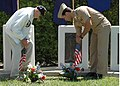 US Navy 060529-N-1159B-031 A veteran and active-duty submariner stand side by side as they place American flags on memorials to U.S. Navy submarines.jpg