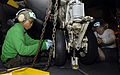 US Navy 081020-N-4954I-003 Aviation Structural Mechanic 3rd Class Amber Scott and Aviation Structural Mechanic 3rd Class Mike Vaneerde tighten screws on the landing gear of an E-2C Hawkeye.jpg