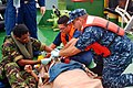 US Navy 100422-N-1401J-115 Medical give emergency first aid to an injured sailor aboard a foreign vessel.jpg