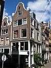 foto van Hoekhuis met klokgevel en op gesneden puibalk overgebouwde gepleisterde zijgevel waarin nog overblijfselen van een versiering in de trant met kleine blokjes
