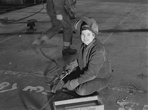 Rosie the Riveter/World War II Home Front National Historical Park - A welder looks up from her work at Richmond shipyard, 1943
