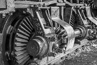 Geared steam locomotive - A wheel on a geared steam locomotive. A shaft (seen towards the right of the photo) transferred power to a bevel gear (partially visible under a cover), which transferred power to the wheel. This wheel is on a Shay locomotive.