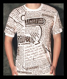 A boy standing in a shirt with wikipedia entries and captions printed all over it.