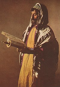 A Yemeni Jew wearing a kippah skullcap prays with a tallit shawl. The prayer box strapped to his forehead and arm are tefillin. His uncut side-curls are payot.