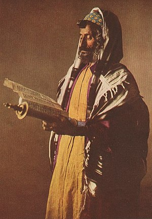 Yemenite Jews - 1914 photograph of a Yemenite Jew in traditional vestments under the tallit gadol, reading from a scroll.