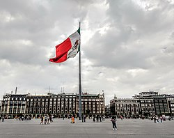 The Zócalo also known as Plaza de la Constitución with the Mexican flag waving in the center and to the right behind it, the Old Portal de Mercaderes