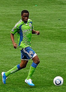 Zakuani dribbles a ball down the field while wearing a Sounders kit