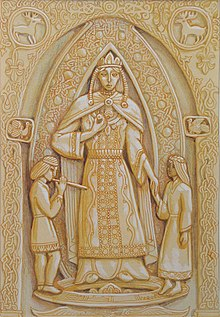 Ornately decorated artwork resembling a wood carving of a robed woman flanked by a boy and girl