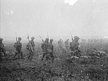 Troops carrying rifles march across a field