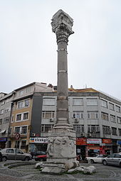 Color photograph of an ancient stone column set in front of a modern building and parked cars. The bottom and top of the column are engraved, and several metal bands placed at regular intervals encircle the central section of the column.