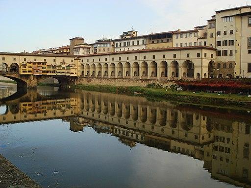 Corridoio Vasari e gli Uffizi si specchiano nell'Arno. Sulla sinistra, Ponte Vecchio