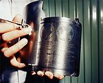 A technician holds the Apollo 11 plaque with the hinged cover open prior to installation on the LM ladder strut.jpg