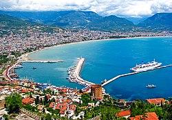 Красочный город с красными крышами поднимается из изогнутой гавани с голубой водой и круизный корабль пристыкован длинным пирсом.