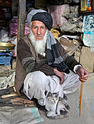 An Afghan elder and his cat sit outside his store at the Anaba bazaar in Panjshir province, Afghanistan.jpg