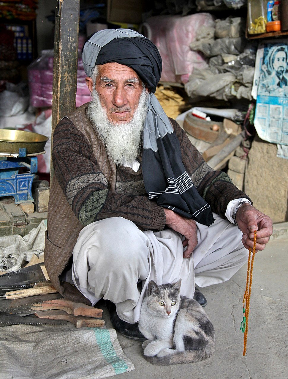 An Afghan elder and his cat sit outside his store at the Anaba bazaar in Panjshir province, Afghanistan