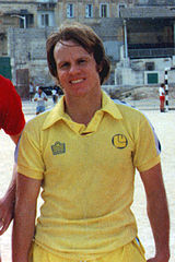 An upper-body photograph of a man with medium-length brown hair wearing a yellow shirt.